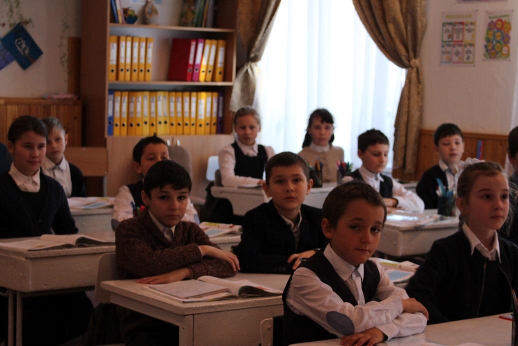 Elevii clasei a IV-a participă la o lecție deschisă.